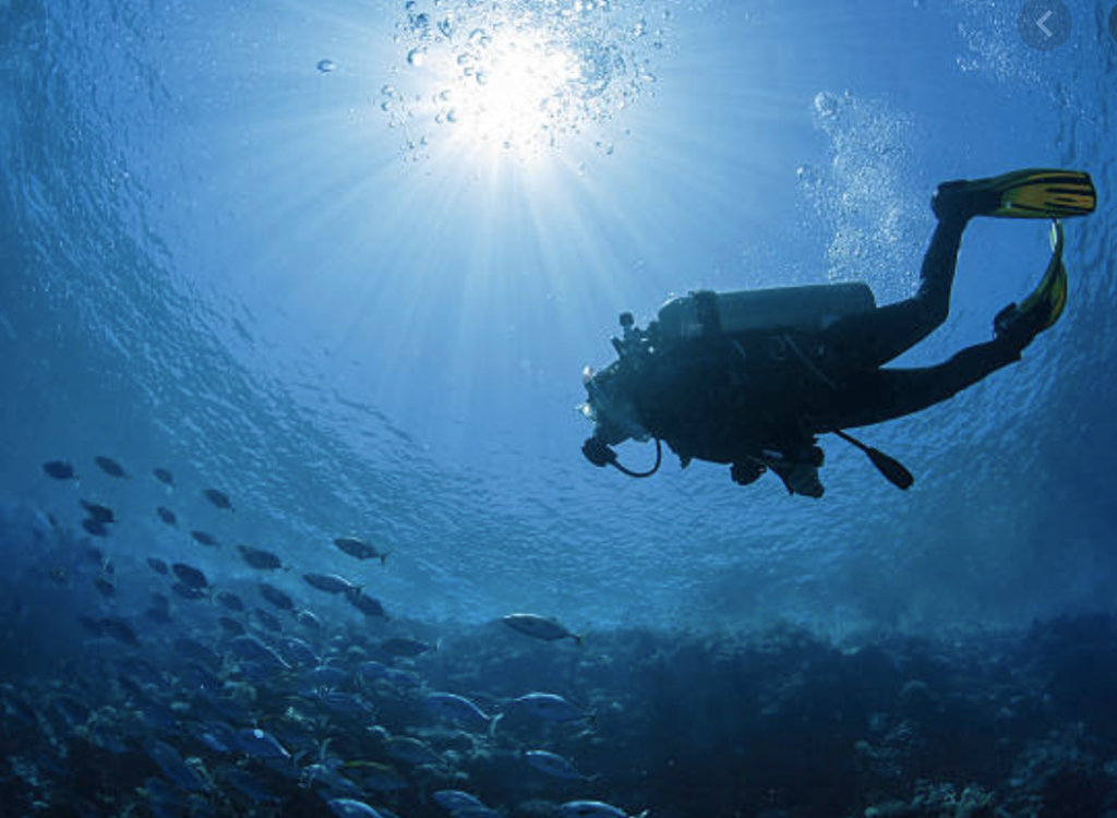 diver with tank in deep waters
